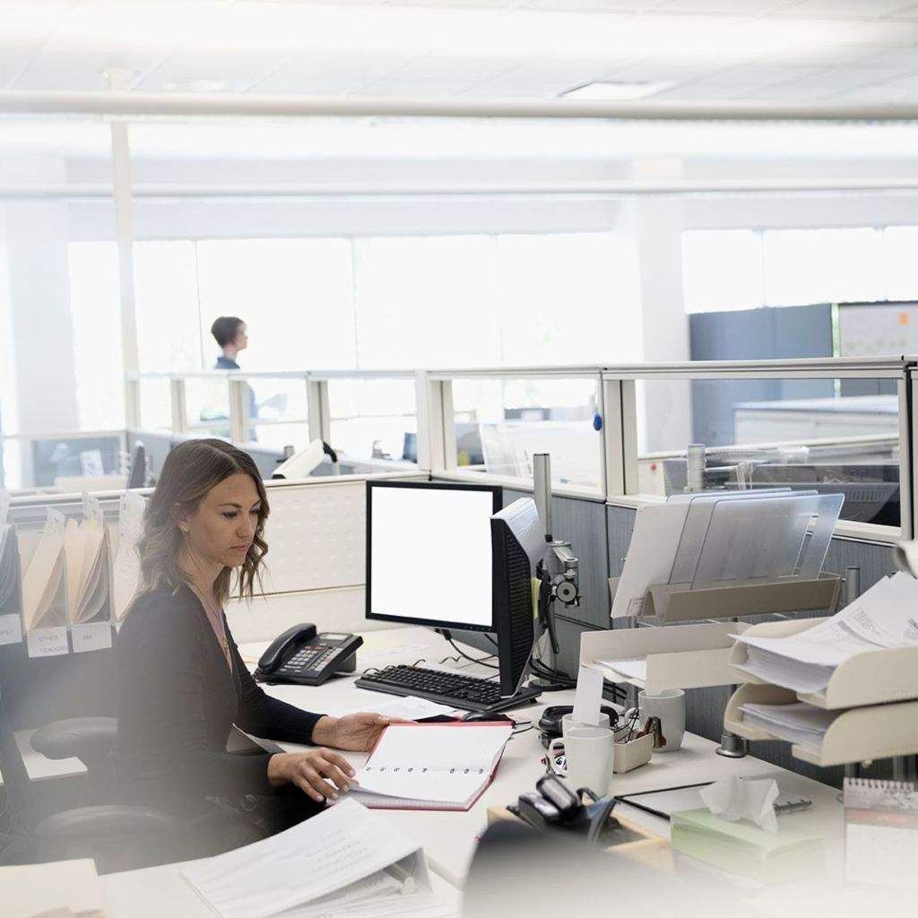 Digitization: Three employees are in an open-plan office; a woman is sitting between papers and her computer
