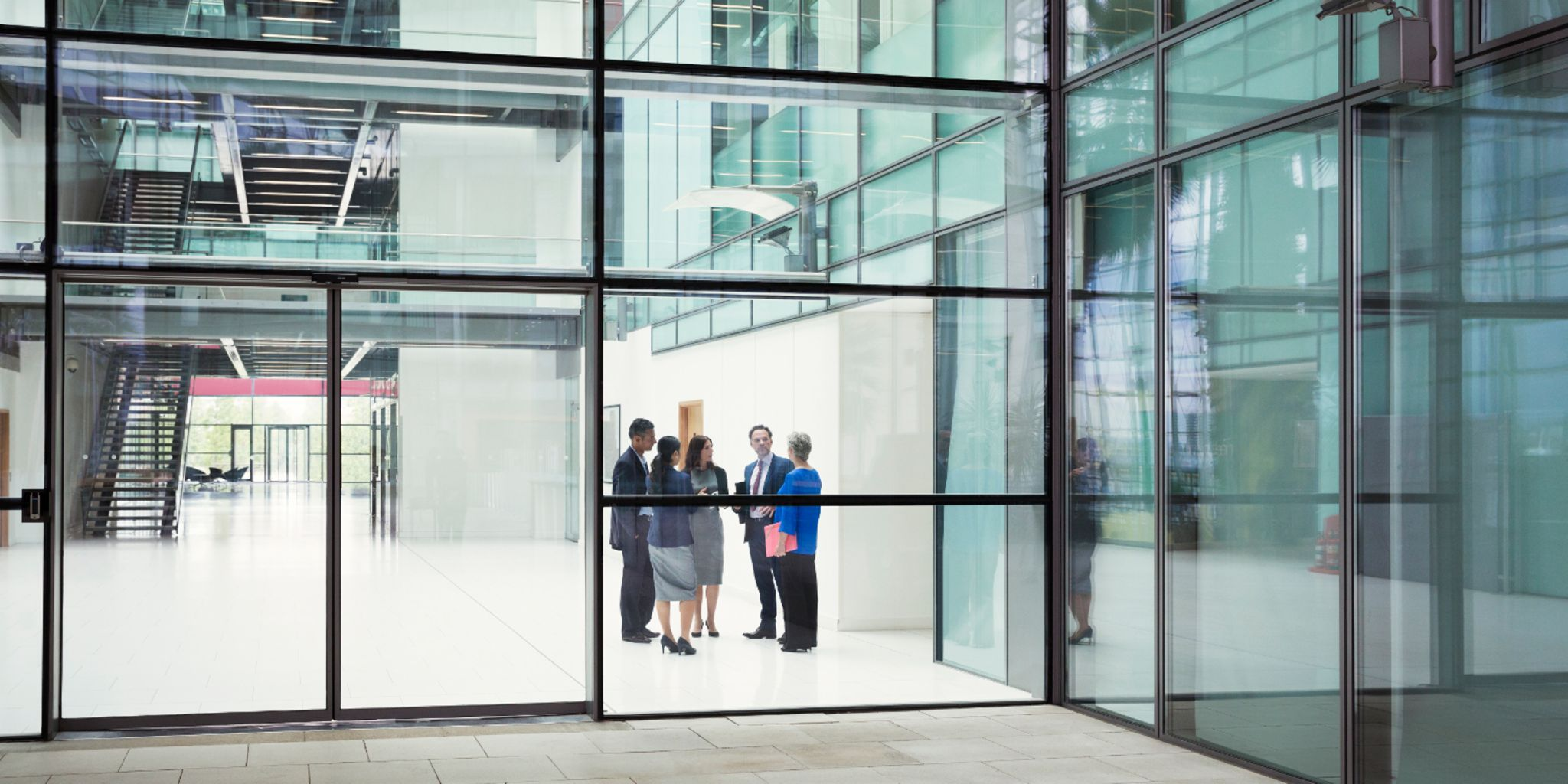 The sale of non-performing real estate portfolios: People standing in the entrance of an office building.