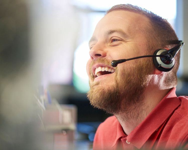 A young man with a headset smiles while on the phone.