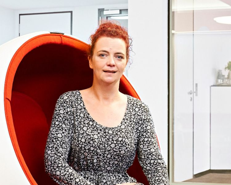 Interview: Call center agent Katja Wolf sitting in an armchair.